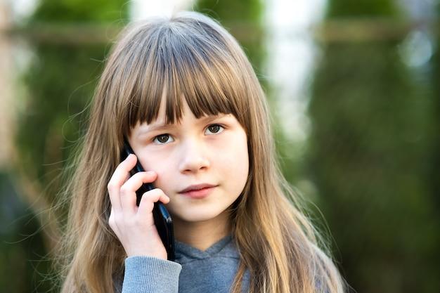 Retrato de niña bonita con cabello largo hablando por teléfono celular. niña pequeña comunicándose con smartphone.