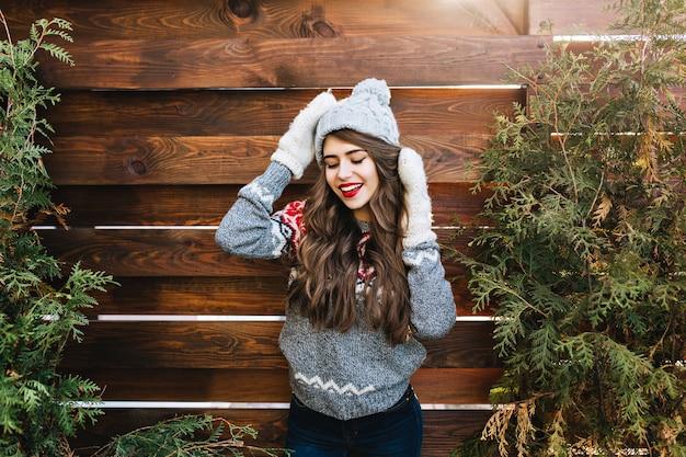 Retrato de niña bonita con cabello largo y labios rojos en gorro de punto y guantes calientes en madera. ella sonríe y mantiene los ojos cerrados.