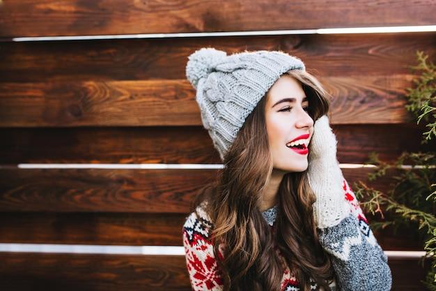 Retrato de niña bonita con cabello largo y labios rojos en gorro de punto y guantes calientes en madera. ella está sonriendo a un lado.
