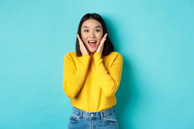 Retrato de niña bonita coreana recibe noticias sorprendentes, mirando sorprendido y feliz a la cámara, de pie sobre fondo azul.