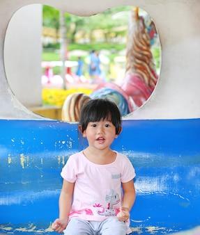 Retrato de una niña bonita de dos años en un carruaje en un carrusel