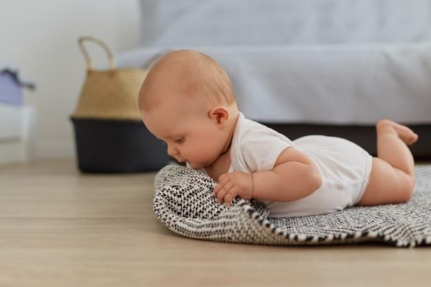 Retrato de niña bonita gateando posando en el interior del piso, estudiando el mundo alrededor, niño pequeño con traje blanco, acostado sobre una alfombra gris cerca del sofá.
