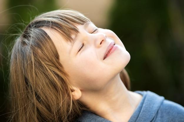 Retrato de niña bonita joven con el pelo largo disfrutando de cálido día soleado en verano al aire libre. lindo niño femenino relajante en aire fresco afuera.