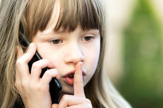 Retrato de niña bonita niña con cabello largo sosteniendo su dedo lo labios en gesto de silencio hablando por teléfono celular