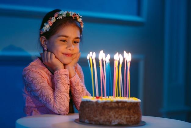 Retrato de niña bonita con pastel de cumpleaños