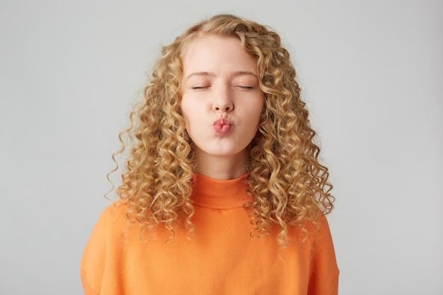 Retrato de niña bonita rizada enviando beso al aire con labios fruncidos y ojos cerrados aislados en la pared blanca