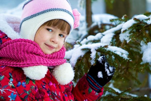 Retrato de niña bonita en ropa de invierno cerca de pino cubierto de nieve