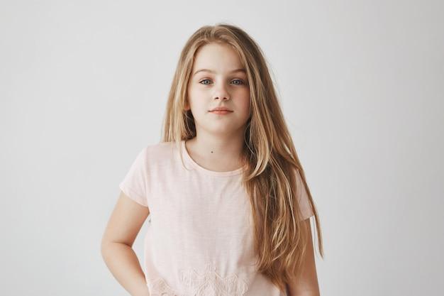 Retrato de niña bonita rubia con el pelo largo en pijama rosa. el niño se levantó temprano, preparándose para la escuela con expresión somnolienta.