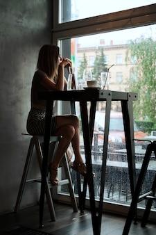 Retrato de niña bonita sentada en el bar y mirando a la ventana