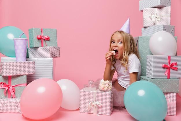 Retrato de una niña bonita en un sombrero de cumpleaños celebrando