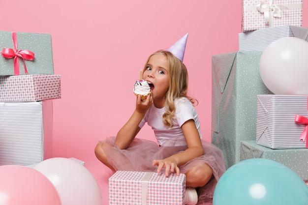 Retrato de una niña bonita con un sombrero de cumpleaños