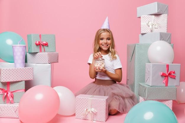 Retrato de una niña bonita sonriente en un sombrero de cumpleaños