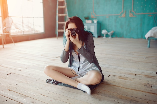 Retrato de niña bonita tomando foto en la cámara de cine