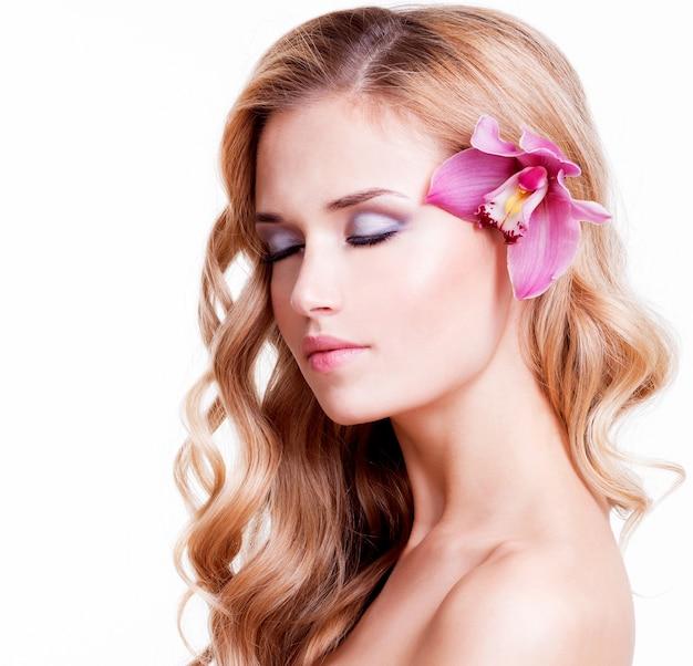 Retrato de niña bonita tranquila con orquídea rosa en el pelo - aislado en blanco.