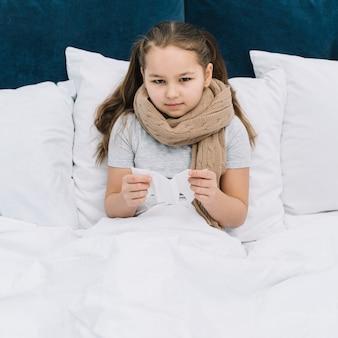 Retrato de una niña con bufanda alrededor de su cuello sosteniendo papel de seda en la mano