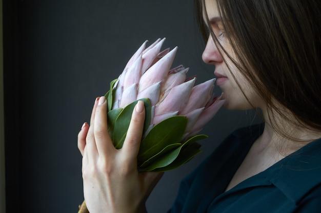 Retrato de una niña con cabello oscuro sostiene una enorme flor rosa de protea