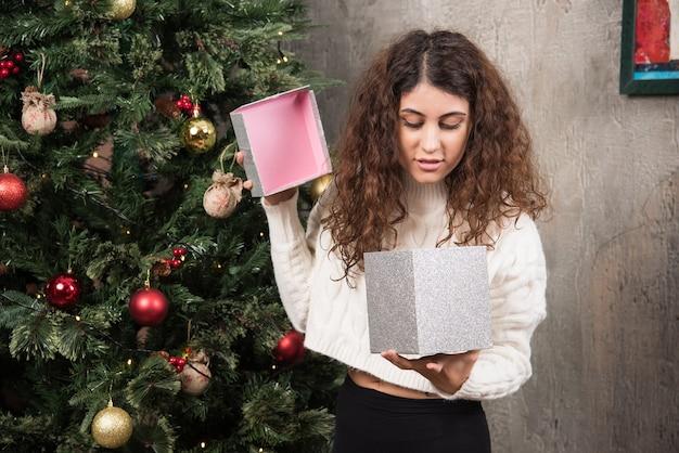 Retrato de niña con cabello rizado abriendo una caja con regalo