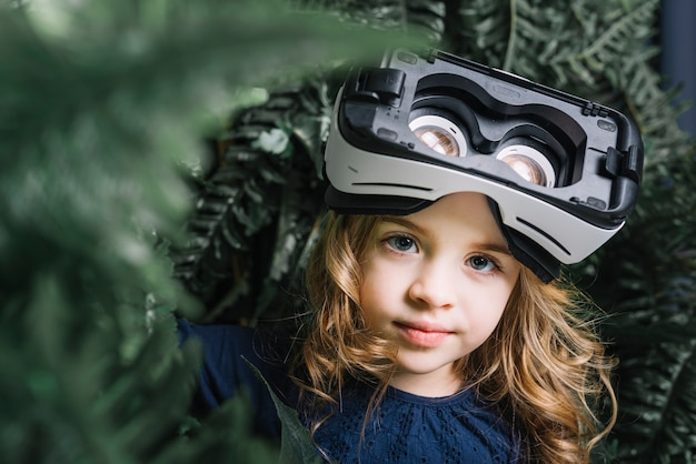 Retrato de una niña con cámara de realidad virtual en su cabeza mirando a cámara
