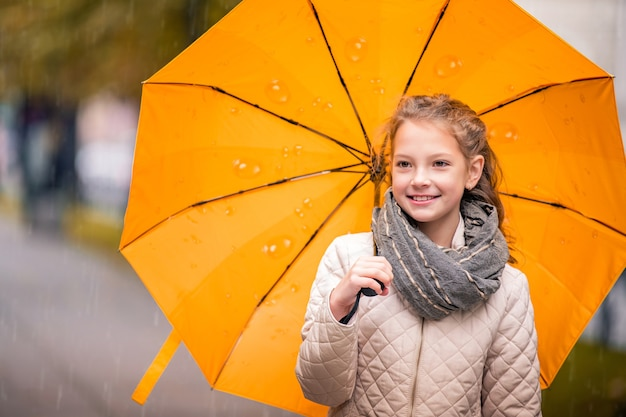 Retrato de una niña caminando bajo un paraguas amarillo brillante en la ciudad de otoño