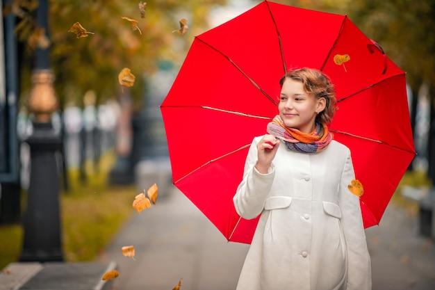 Retrato de una niña caminando bajo un paraguas rojo brillante en la ciudad de otoño