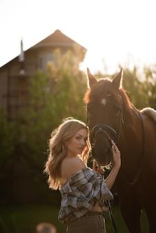 Retrato de niña camisa inplaid con caballo negro en la granja de caballos