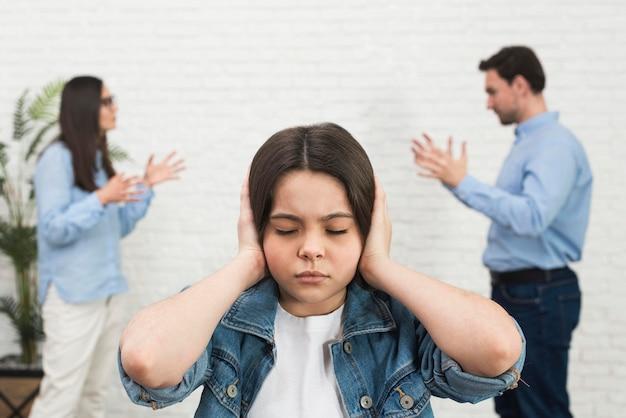 Retrato de niña cansada de padres discutiendo