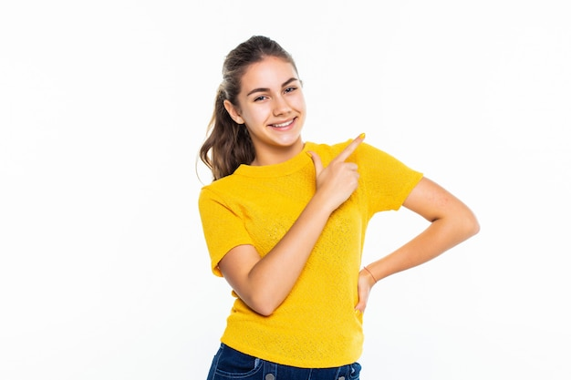 Retrato de una niña casual feliz apuntando contra la pared blanca