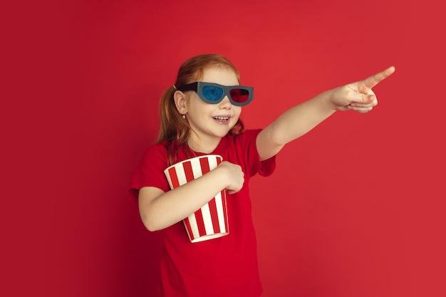 Retrato de niña caucásica aislado en estudio rojo
