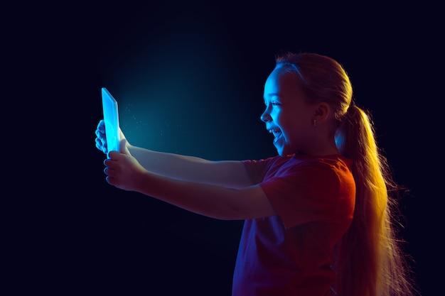 Retrato de niña caucásica aislado en la oscuridad en luz de neón