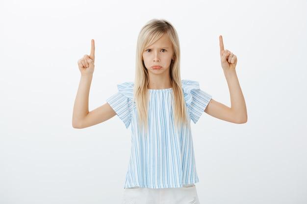 Retrato de una niña caucásica enojada ofendida con cabello largo y rubio, haciendo pucheros y enfurruñado, levantando los dedos índices y apuntando hacia arriba, viendo algo decepcionante e insultante sobre la pared gris