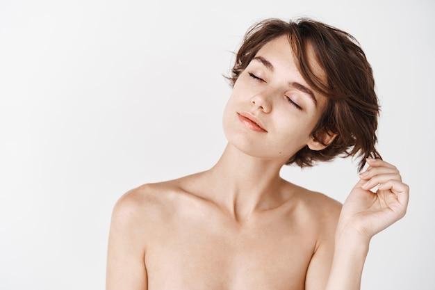 Retrato de niña caucásica con peinado corto y cuerpo desnudo, tocando el cabello con los ojos cerrados y mirada soñadora, duchándose o aplicando productos para el cuidado de la piel, pared blanca