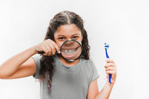 Retrato de una niña con cepillo de dientes y lupa mostrando sus dientes