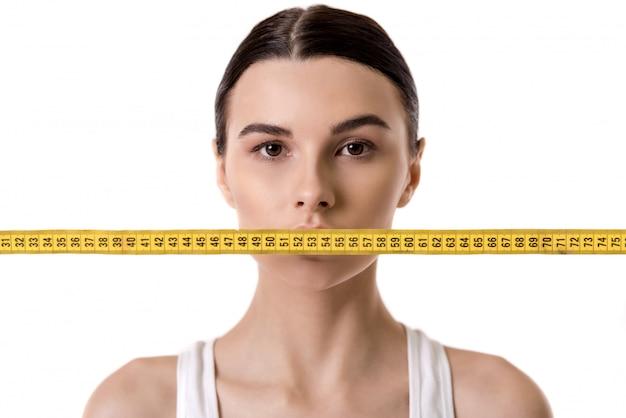 Retrato de niña con una cinta métrica delante de su boca. concepto de dieta