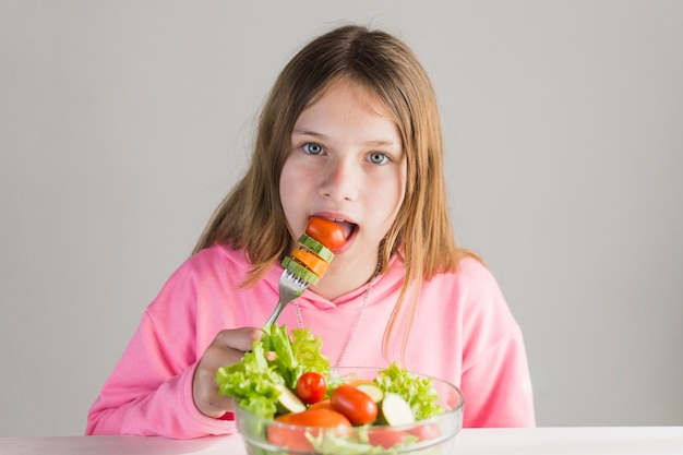 Retrato de niña comiendo ensalada saludable con tenedor