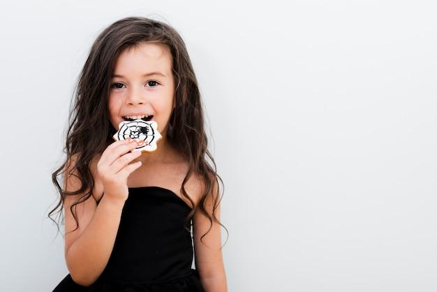 Retrato de una niña comiendo una galleta
