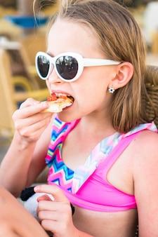 Retrato de niña comiendo pizza en un café al aire libre en la cena