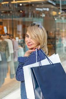 Retrato de niña de compras de moda. mujer de belleza con bolsas de compras en el centro comercial. comprador. ventas.