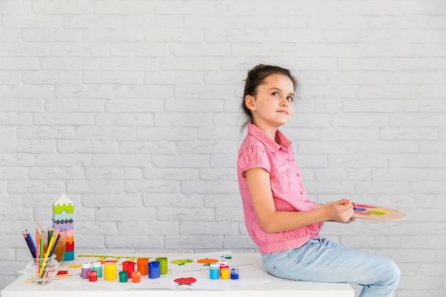 Retrato de una niña contemplada sentada en la mesa blanca mezclando la acuarela en la paleta