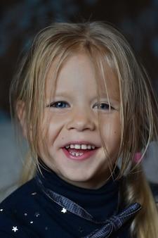 Retrato de una niña con una corbata de lazo riendo, boca abierta, fondo oscuro