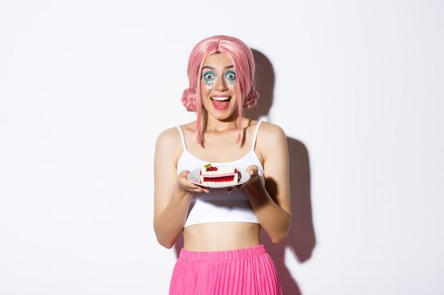 Retrato de niña de cumpleaños emocionada celebrando, con peluca rosa, sosteniendo el pastel de cumpleaños y sonriendo feliz, de pie.