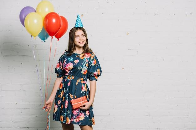 Retrato de una niña de cumpleaños con globos y caja de regalo mirando a otro lado