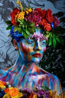 Retrato de una niña cuyo rostro está pintado con pinturas de colores en una corona de flores. en los pasos de frida kahlo