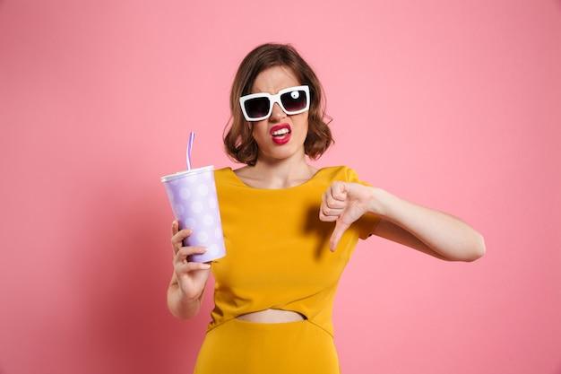 Retrato de una niña decepcionada en gafas de sol con taza