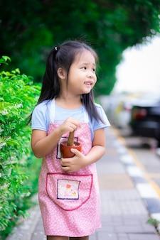 Retrato de niña en delantal con mortero en el parque