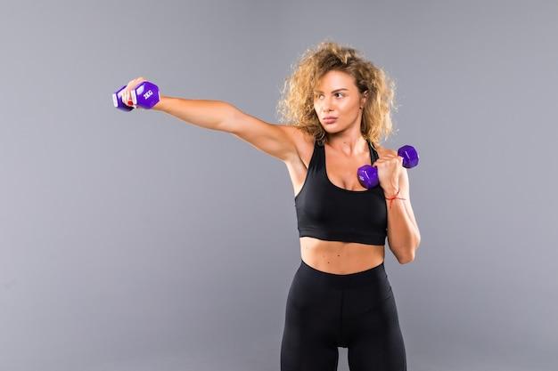 Retrato de niña deportiva bastante rizado sosteniendo pesas mancuernas aislado en la pared gris
