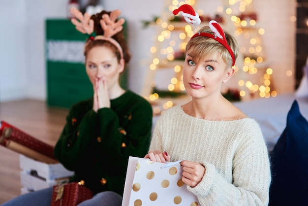 Retrato de niña disgustada abriendo regalo de navidad