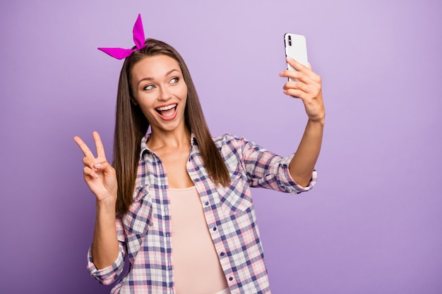 Retrato de niña divertida tomar selfie hacer v-sign