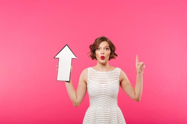 Retrato de una niña emocionada vestida con vestido apuntando hacia arriba