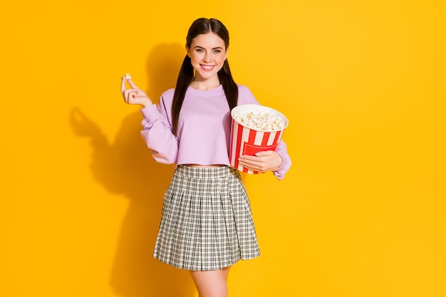 Retrato de niña encantadora alegre ver películas mantenga comer gran caja de palomitas de maíz