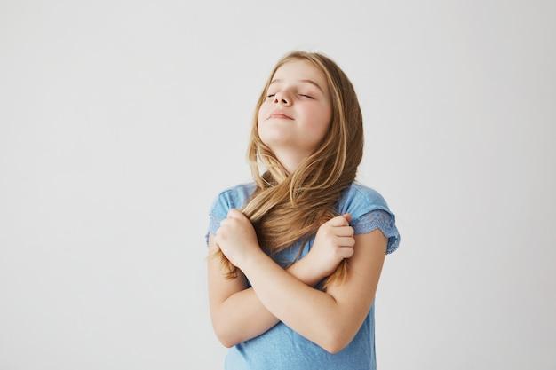 Retrato de niña encantadora con cabello claro en camiseta azul divertida posando para la foto con los ojos cerrados, tomando su cabello en las manos y cruzándolos.
